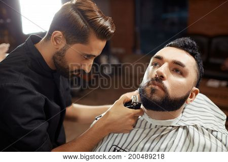 Young man working with client and shaving his beard in barbershop.