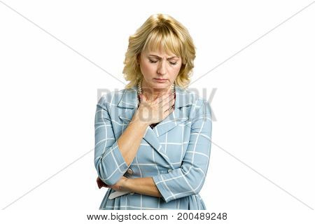 Mature woman feeling sore throat. Unhappy middle aged woman putting hand near throat isolated on white background.