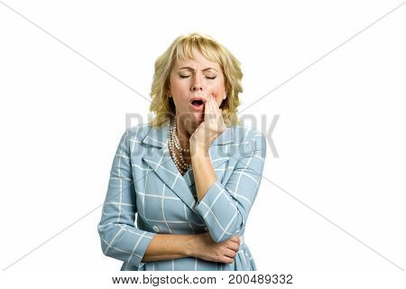 Middle aged woman having terrible tooth pain. Attractive middle aged woman suffering from terrible strong teeth pain, touching cheek with closed eyes standing on white background.