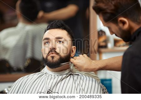 Anonymous man grooming beard of young man sitting in chair in barbershop.