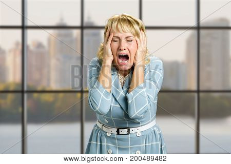 Portrait of screaming desperate woman. Close up shot of stressed and frustrated white-skin woman screaming with desperate and horrified expression, office window background.