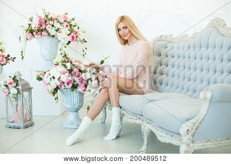 Happy Blonde And Sexy Young Woman Siting On The Retro Bed With A Beautiful Autumn Or Spring Flowers.