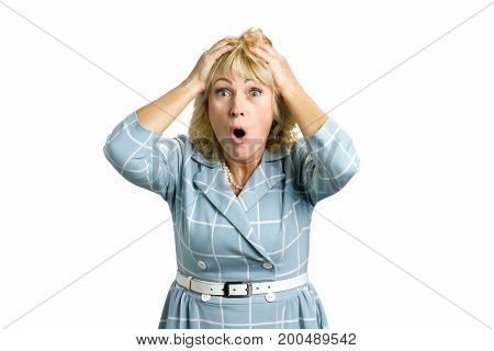 Surprised mature woman on white background. Closeup portrait of white-skin woman looking surprised in full disbelief with hands on hand and open mouth on white background.