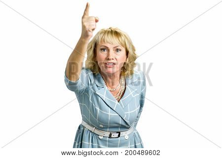 Frustrarted woman raised hand up. Annoyed mature woman pointing upward, white background. Angry blond woman scolding someone and pointing with her finger upward, proving arguments isolated on white.