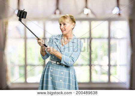 Woman with monopod, blurred background. Beautiful middle aged woman taking picture with selfie stick.