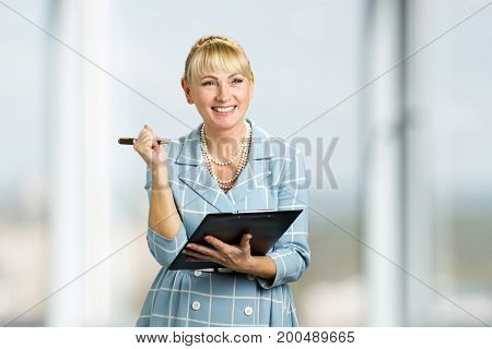 Smiling lady with clipboard and pen. Portrait of cheerful mature woman holding clipboard, pen and smiling.