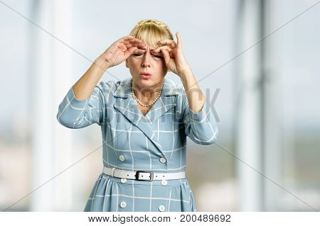 Drowsy mature woman in dress. Sleepy tired white-skin woman rubbing her eyes by hands on blurred background.