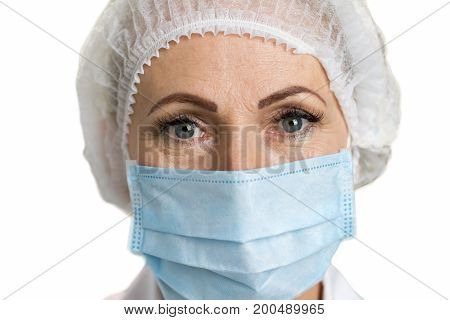 Detail of female mature doctor. Female white-skin doctor close up wearing mask, white background. Medical and healthcare concept.