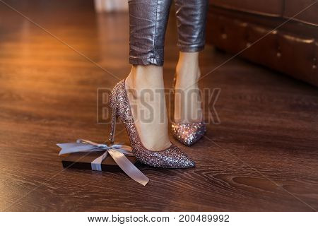 Box In Special Gift. Beautiful Legs And High-heeled Shoes. Box With Present Laying On The Floor