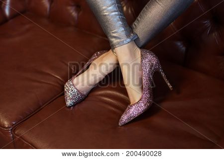 Beautiful High-heeled Glitter Shoes On A Leather Sofa. Beautiful Unusual Shoes.