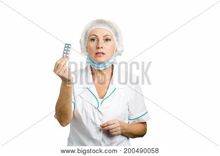 Beautiful female doctor showing pills. White-skin mature woman doctor prescribing medicine and giving blister of pills standing on white background.