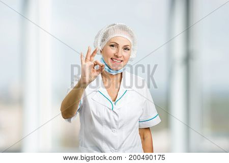 Smiling female surgeon gesturing ok. Cheerful beautiful mature woman doctor showing ok gesture over blurred background.