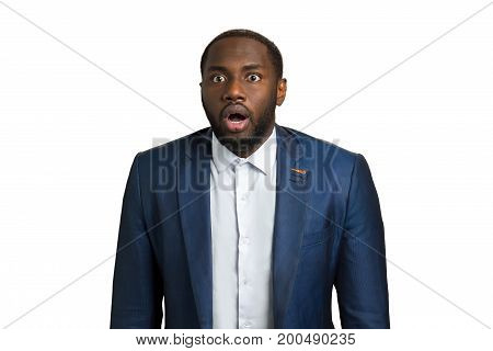 Black man with astonishment. Surprised afro american manager in suit on white background. Emotions of amazement and wonderment.