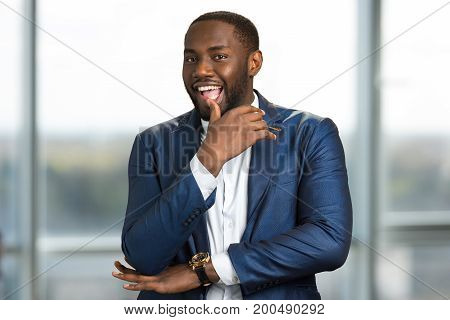 Playful afro american businessman. Young black businessman with an intriguing smile. Have got an interesting idea.