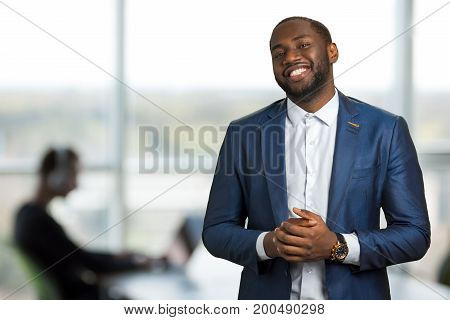Smiling black businessman in office. Afro american man in suit in good mood. Handsome black manager of company smiling on blurred background.