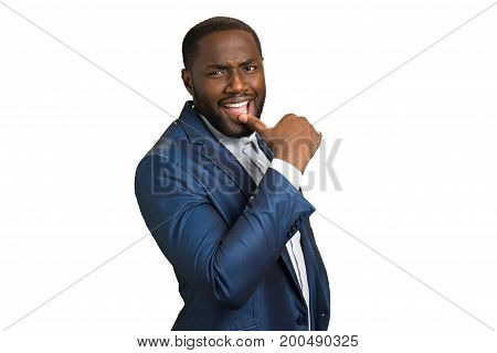 Businessman smile with squinty look. Young afro american businessman hold finger on lips and thinking. Thoughtful and positive executive.
