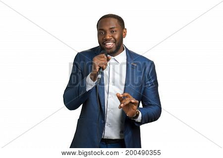 Black man smiling and singing. Black guy in suit with microphone. Elegant jazz artist. Afro american artist in studio.