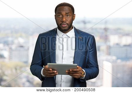 Suprised businessman with computer tablet. Sad black manager hold digital tablet on blurred background. Business owner in bewilderment with pc tablet in hands.
