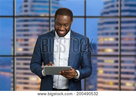 Happy businessman on skyscraper background. Smiling afro american manager types a message on computer tablet. Positive emotions of young executive from internet communication.