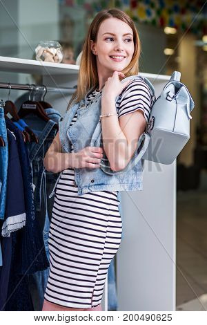 Young smiling female model posing in a showroom in stylish casual summer outfit with a backpack.
