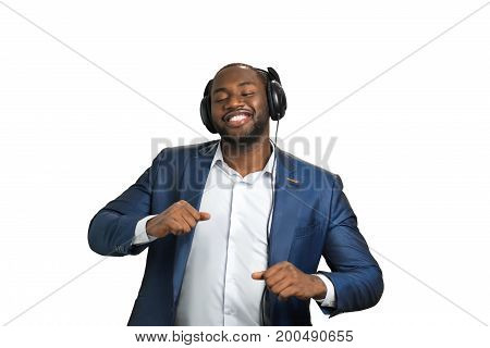 Expressive afro american manager with headphones. Handsome black businessman listening to music and dancing on white background. Working day with positive and qualitative sound.