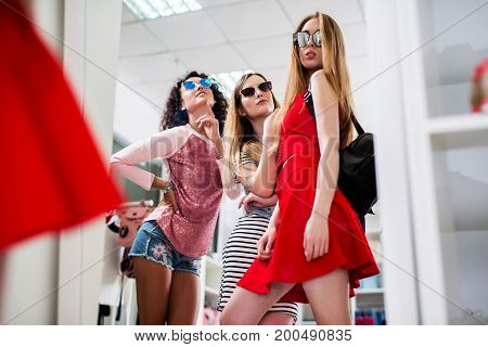 Low-angle shot of stylish glamorous girlfriends choosing new clothes and sunglasses standing posing in front of the mirror in showroom.