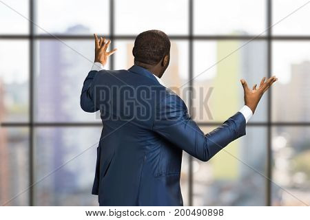 Businessman from back raising hands. Rear view of angry manager in front of modern office window holding arms out wide. Holds hands upwards.