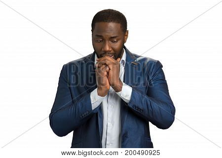 Unhappy businessman looking down. Thoughtful black man holding hands near mouth. Searching for right decision.