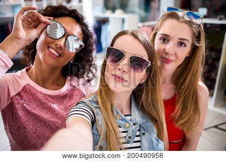 Smiling girlfriends wearing stylish sunglasses having fun time taking selfie with mobile phone while doing shopping in clothing store.