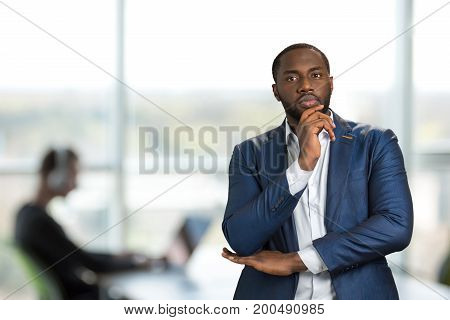 Serious businessman hold chin on hand. Handsome young manager thinking about serious idea. Confident entrepreneur thinking about important solution.