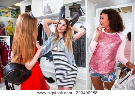 Group of girlfriends spending time together having fun doing shopping. Pretty girl showing ears with shoes in fashion store.