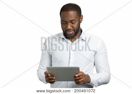 Man in shirt using computer tablet. Bearded businessman looking down at digital tablet on white background.