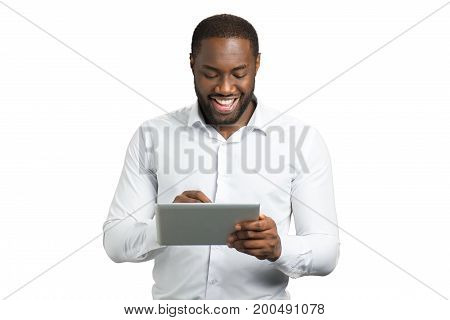 Elated businessman using pc tablet. Happy afro american entrepreneur working on touch screen tablet on white background.