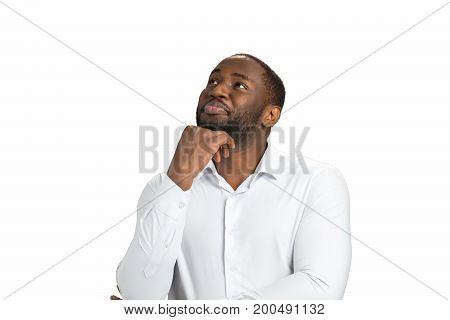 Thinking businessman on white background. Smiling man sitting and holding chin on hand. Lost in positive dreaming.