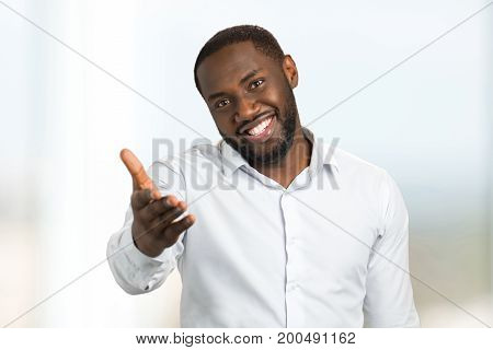 Black man in shirt pointing hand forward. Hand gesture and facial emotions of afro american man in white shirt.