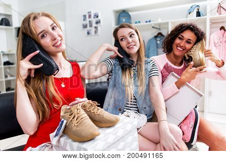 Pretty close friends doing shopping together holding new shoes as phones in fashion store.