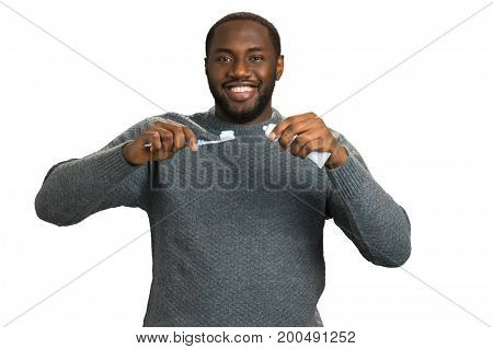Man looking straight with toothpaste. Smiling black man in grey sweater hold toothpaste and toothbrush. Oral health care.