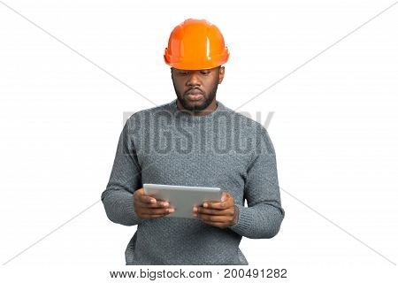 Male engineer looking at computer tablet. Afro american young architect hold computer tablet on white background. Checking some information.