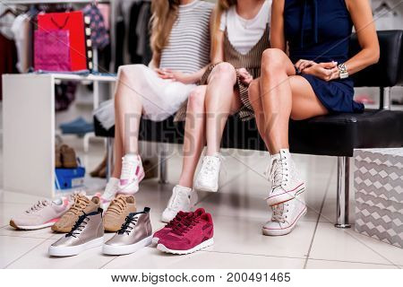 Girls choosing teen shoes surrounded by youth footwear at trendy clothing shop.