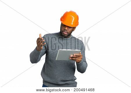 Young male engineer gesticulating with tablet. Dark skinned constructor with tablet raised hand with amazement on white background. poster