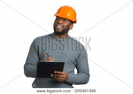 Foreman in casual wear checking object. Positive young architect looking at building and writing. Beautiful architect in orange helmet.