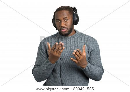 Man in casual wear with headphones. Confused afro american guy in headphones waiting for music on white background.