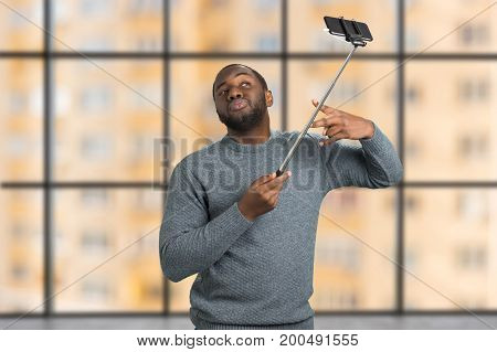 Young casual handsome man using selfie stick. Attractive man playfully taking selfie with monopod on blurred background. Young black man makes photo on monopod.