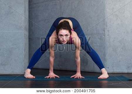 Young fit woman standing in wide-legged forward bend doing pilates exercises looking at camera in fitness club.
