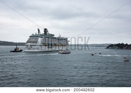 SYDNEY,NSW,AUSTRALIA-NOVEMBER 19,2016: Royal Caribbean cruise ship with tugboat and other vessels in the Parramatta River in the harbour in Sydney, Australia.
