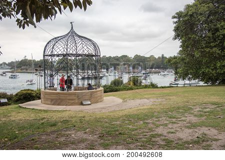 SYDNEY,NSW,AUSTRALIA-NOVEMBER 19,2016: Tourists by metal gazebo at the Royal Botanic Gardens overlooking nautical vessels at Farm Cove for The Plot 2016 concert in Sydney, Australia