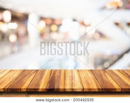 Empty wooden table with blur shopping mall background. For display or montage your products.