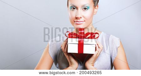 Young woman happy smile hold gift box in hands, isolated over grey background.