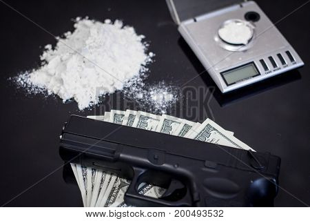 illegal drugs, money and hand gun on black table