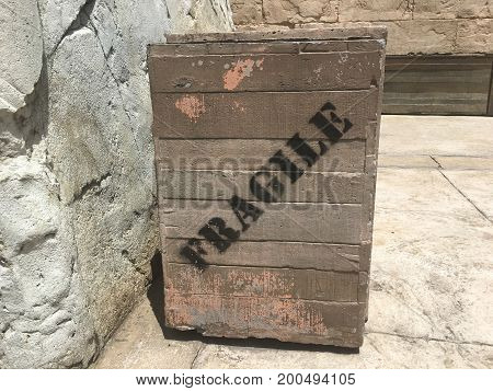 Used Wood crate written Fragile in diagonal in black on the ground